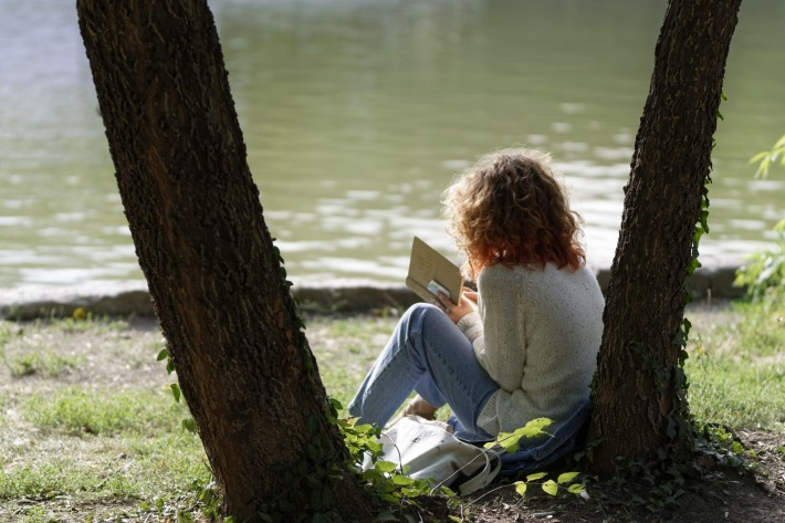 Girl reading a book next to trees
